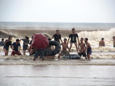 Du khách vẫn chụp ảnh tự sướng dưới tâm bão tại biển Sầm Sơn. Ảnh: Lao động