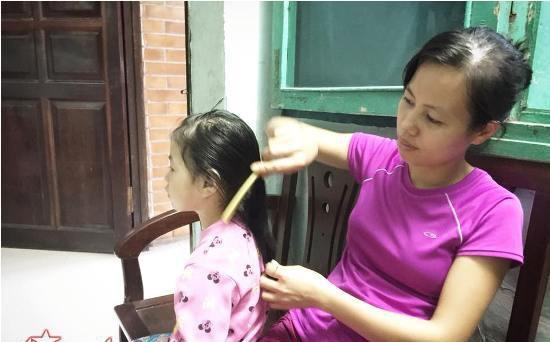 Chị Thảo ân cần chải tóc cho bé Na.     Ảnh: Kiều Hà