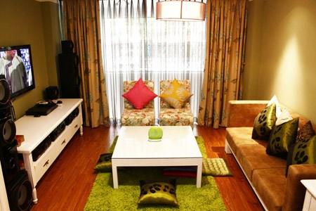 Phòng khách ấm cúng và yên tĩnh với tông màu trắng, điểm nhấn là tấm thảm trải sàn màu xanh.