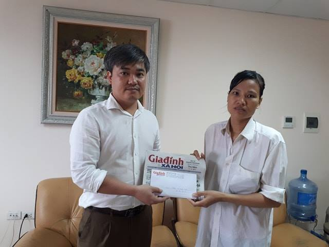 Ông Trần Tuấn Linh - Phó Tổng biên tập Báo Gia đình & Xã hội trao tiền cho mẹ bé Triển. Ảnh PT