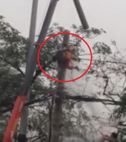 Thợ điện bị dòng điện phóng trúng dẫn đến bốc cháy, nằm lắc lư trên cột điện. Ảnh cắt từ clip