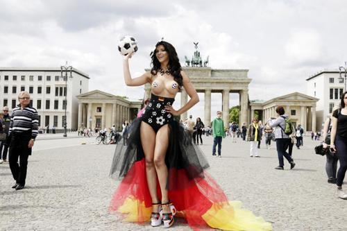 """Trong mùa World Cup 2014, đường phố Berlin từng được phen náo loạn vì màn """"thả rông"""" ngực khủng để cổ vũ tinh thần các tuyển thủ đội tuyển quốc gia Đức của cô ca sĩ kiêm diễn viên, DJ Micaela Schaefer.  Theo đó, người đẹp để ngực trần, che nhũ hoa bằng miếng dán hình quả bóng rồi thoải mái tạo dáng, đi lại trên phố trước con mắt của hàng ngàn người dân cũng như du khách."""