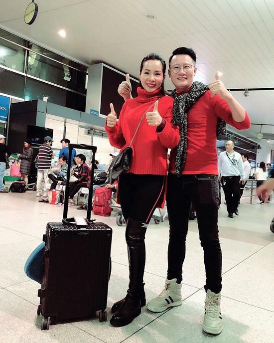 Vợ chồng ca sĩ Hoàng Bách mặc ton sur ton áo đỏ, quần đen khi ra sân bay Tân Sơn Nhất vào lúc 4h sáng. Cả hai cùng bay sang Thường Châu để xem trận chung kết và ủng hộ tinh thần của đội tuyển U23 Việt Nam vào chiều nay (27/1).