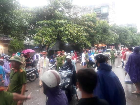 Hàng trăm người dân theo dõi sự việc dưới trời mưa.