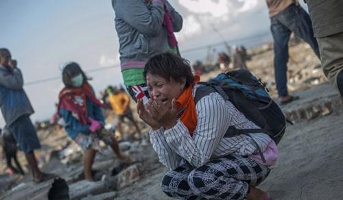 Cư dân tại một ngôi làng ở TP Palu bị động đất tàn phá nặng nề Ảnh: AP