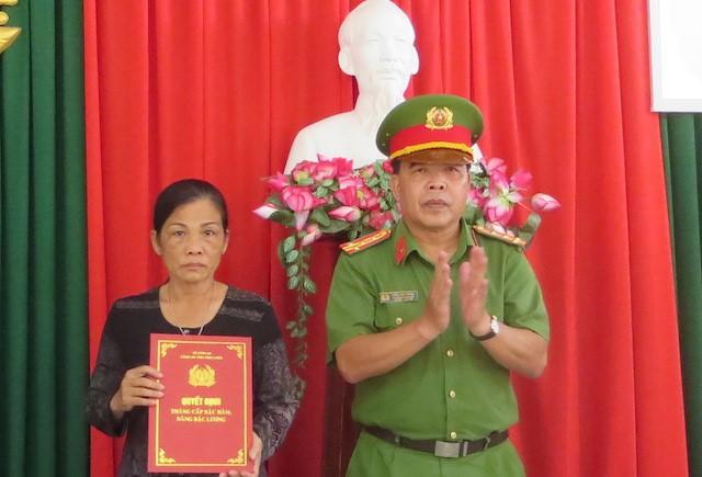 Đại tá Trần Văn Thắng, Trưởng Công an huyện Long Hồ, trao quyết định thăng bậc hàm cho người thân Trung úy Nguyễn Đức Đạt. Ảnh: C.A.