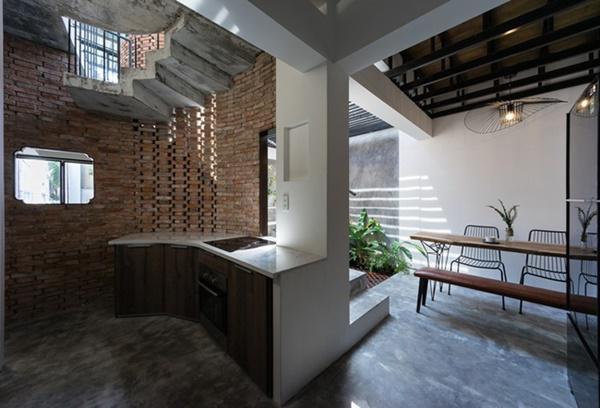 Tủ bếp thiết kế uốn lượn theo hình dáng của tường gạch bên ngoài.