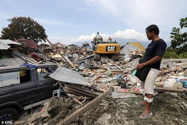 Người dân đau đớn nhìn đống đổ nát sau trận động đất khiến đất hóa lỏng.