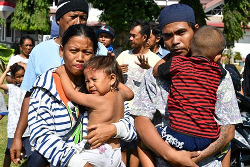 Rahmatia bế con thứ hai trong khi chồng cô bế con trai Jumadil trong ngày đoàn tụ. Ảnh: AFP