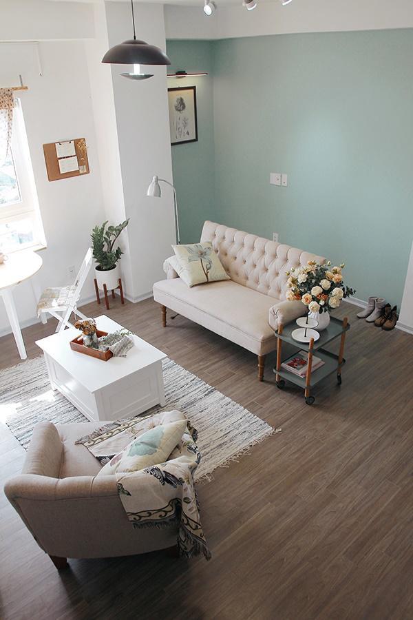 Phòng khách được trang trí với tông màu pastel pha với màu gỗ tạo cảm giác ấm cúng.