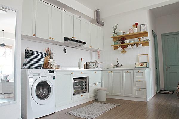 Phòng khách thông với phòng bếp và cùng có tông màu trắng.