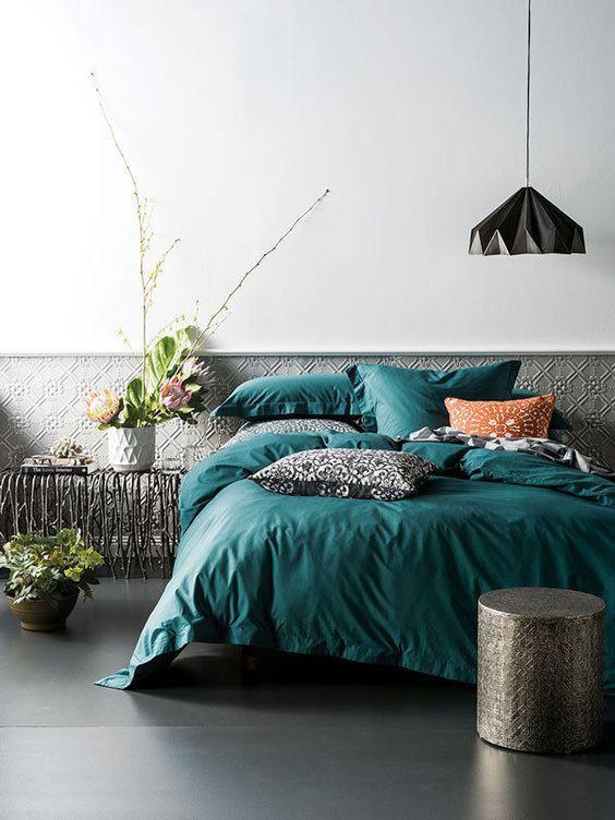 Giường màu ngọc lục bảo với những chiếc gối có hoa văn và những chiếc gối màu đen đem đến sự táo bạo.