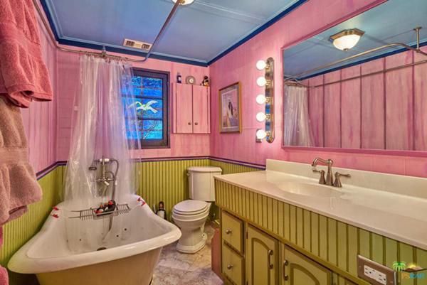 Phòng tắm lớn được sơn màu hồng, có bồn rửa lớn và bồn tắm đứng.