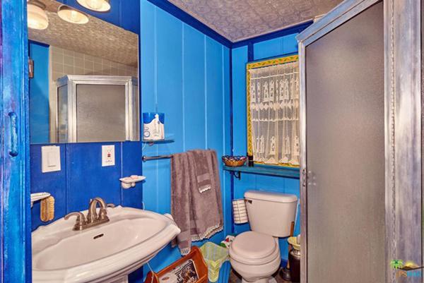 Phòng tắm nhỏ được sơn màu xanh da trời.