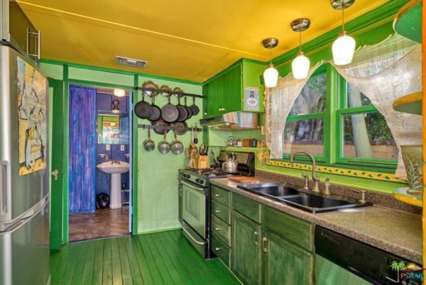 Phòng bếp sơn màu xanh lá với trần màu vàng.