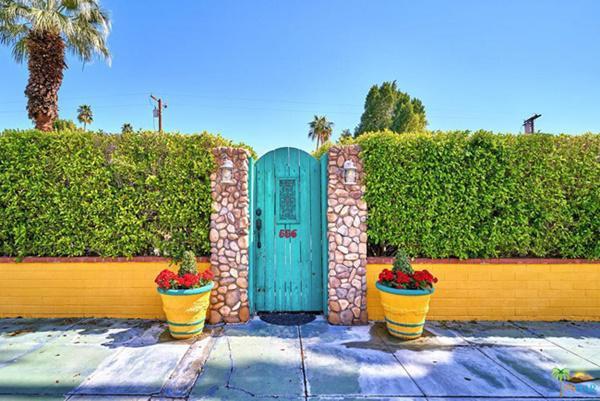 Ngôi nhà gây chú ý ngay từ hàng rào bằng cây xanh được cắt tỉa gọn gàng, bờ tường gạch sơn vàng rực...