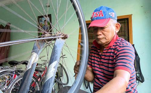 Ông lão sửa xe kiếm tiền lo gia đình cùng chi phí đi học. Ảnh: Thiên Lý.