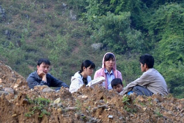 Chị Bùi Thu Trang, vợ của nạn nhân Bùi Văn Thú (thứ 3 từ trái sang) như hoá đá chờ tin chồng nơi lò khai thác vàng trái phép bị sập dưới chân núi Cột Cờ. Ảnh: Nguyễn Mạnh