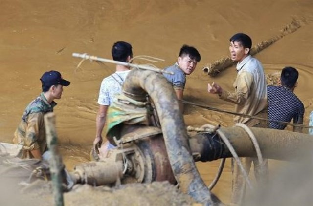 Công nhân bơm hút nước, bùn tìm kiếm hai phu vàng mắc kẹt.