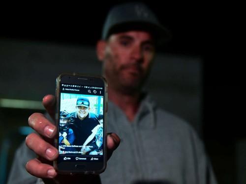 Jason Coffman giơ ảnh con trai Cody, người thiệt mạng trong vụ xả súng tại quán bar ở Thousand Oaks, bang California, Mỹ. Ảnh: AFP.