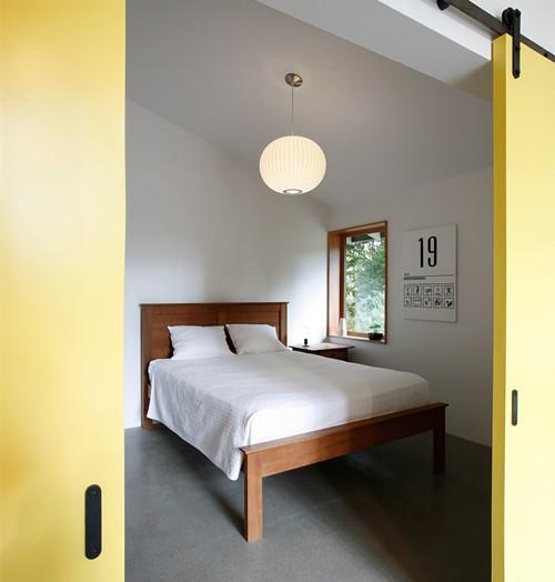 Phòng ngủ được bố trí một đèn trần hình tròn và sử dụng nội thất đơn giản. Cửa sổ nhỏ mang đến cảm giác gần gũi thiên nhiên và xóa tan sự ngột ngạt.
