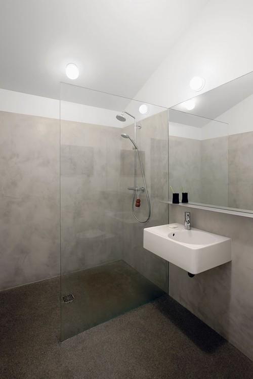 Trong phòng tắm, kiến trúc sư lắp đặt các thiết bị chiếu sáng gọn gàng, hiện đại và các bức tường được bọc xi măng cẩn thận.