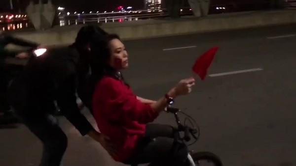 Vất vả đạp chiếc xe tí hon suốt chiều dài cầu Rồng nhưng tinh thần của cô vẫn rất hăng.