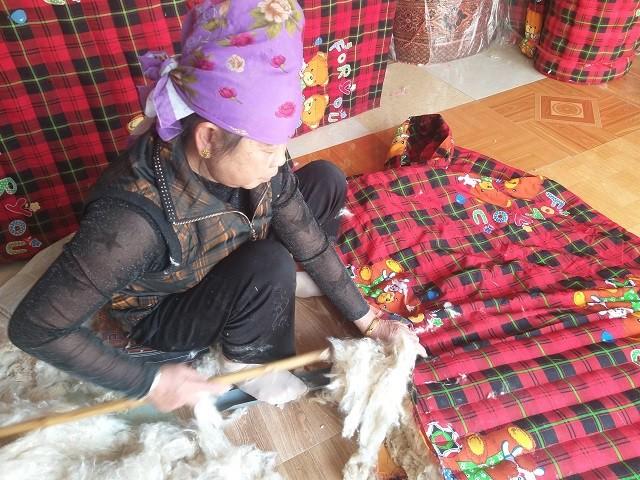 Sau khi cắt 2 khổ vải thành hình chữ nhật theo kích thước của giường, bà Thoa may kín 3 mép. Sau đó bà dùng một cái thanh nhựa nhằm cố định mặt vải phía dưới và một cái gậy tre để đẩy bông vào thân đệm.
