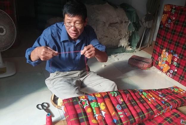 Ông Minh cẩn thận khâu từng đường kim mũi chỉ để những sợi bông không bị lọt ra ngoài, đảm bảo độ chắc chắn cho tấm đệm.