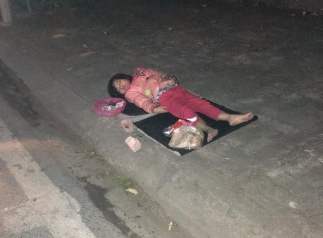 Hình ảnh bé gái 5 tuổi nằm ngủ trên vỉa hè vì quá mệt khiến nhiều người xót xa.