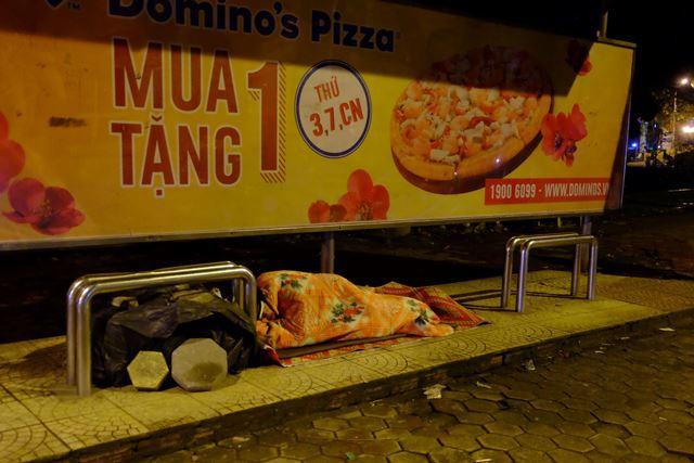 Một người đàn ông trùm chăn ngủ ở nhà chờ xe buýt, hành lý được đè bằng gạch để tránh gió thổi bay. Ảnh: PV
