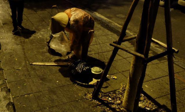 12h đêm nhưng những người bán hàng rong vẫn gánh gánh hàng của mình đi giữa trời mưa lạnh.
