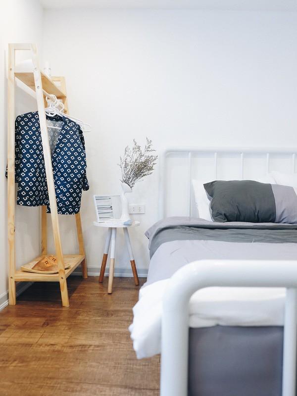 Móc treo quần áo bằng gỗ mộc mạc, kết hợp với chiếc bàn nhỏ xinh đầu giường.