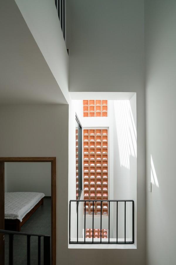 Hai giếng trời ở bên cạnh và cuối nhà cũng hỗ trợ việc đưa ánh sáng và gió tự nhiên vào khắp không gian trong nhà.