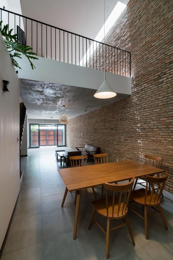 Thay vì để thông tầng ở phía trước như đa số, ngôi nhà phá cách với khoảng thông tầng cuối nhà. Các không gian sinh hoạt chung như phòng khách, phòng ăn, bếp ở tầng trệt và phòng làm việc ở tầng một liên thông với nhau. Đây cũng là một giải pháp giúp nhà thêm thoáng đãng.