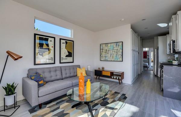 Nhà được sơn màu trắng tạo cảm giác thoáng rộng, nhấn nhá thêm các màu sắc nổi bật khác qua nội thất hoặc đồ trang trí. Không gian tiếp khách được bố trí ngay giữa nhà.