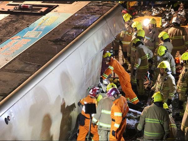 Nhân viên cứu hộ tìm kiếm người kẹt trong chiếc xe lật. Ảnh: South China Morning Post.