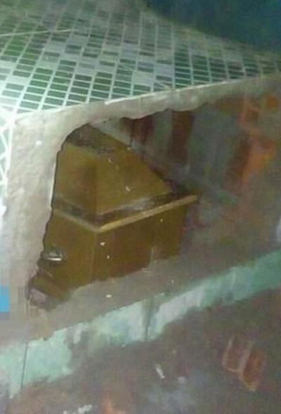 Người nhà đập vỡ ngôi mộ để đưa quan tài Rosangela ra ngoài. Ảnh: Globo