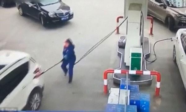 Nhân viên đang kiểm tra đồng hồ bơm xăng thì chiếc xe bất ngờ chuyển bánh.