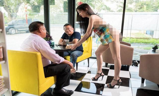Nữ nhân viên phục vụ mặc chiếc tạp dề mỏng manh phục vụ cafe cho khách nam