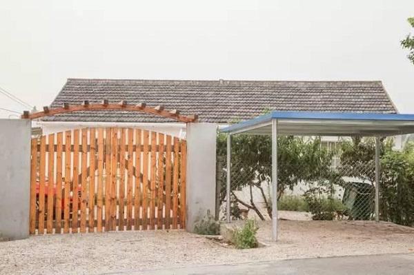 Cô sử dụng chất liệu gỗ làm cổng chính cho nhà và toàn bộ sân vườn xung quanh, bên ngoài còn xây dựng lán để ô tô riêng biệt.