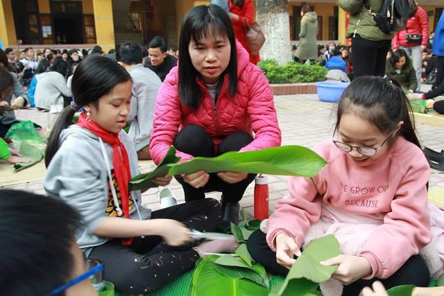 Cô Ngô Xuân Lê - Giáo viên chủ nhiệm lớp 6A1 hướng dẫn học sinh gói bánh Chưng.