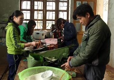 Giáo viên trường Phổ thông Dân tộc Bán trú THCS Nậm Càn gói bánh cho học sinh đón tất niên. Ảnh: Báo Nghệ An.
