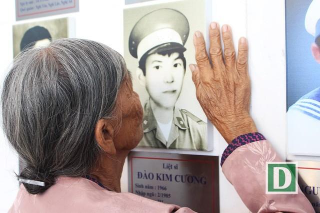 Mẹ liệt sĩ Đào Kim Cương (Hà Tĩnh) run run đặt bàn tay lên di ảnh con tại Khu tưởng niệm Chiến sĩ Gạc Ma
