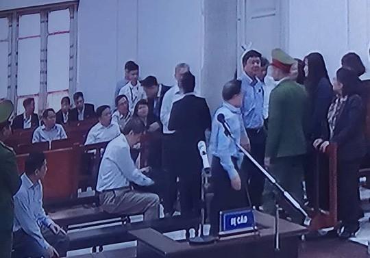 Ông Thăng đứng trò chuyện với những n]ời xung quanh trong khi HĐXX hội ý về việc một số nhân chứng liên quan đến vụ án được tòa triệu tập nhưng vắng mặt. Ảnh: HC