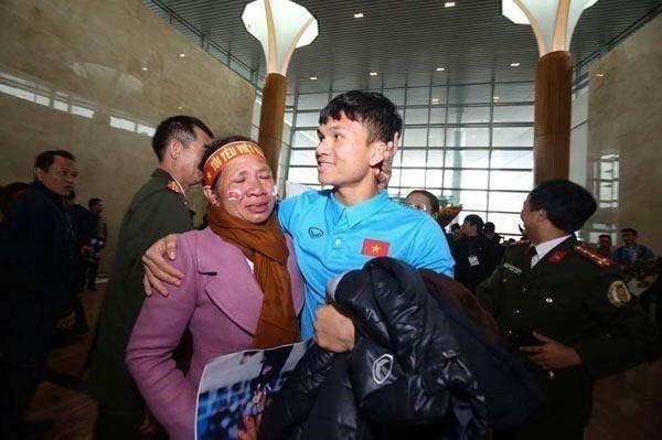 Hình ảnh hậu vệ phải Xuân Mạnh bế mẹ ở Nội Bài gây xúc động trong lòng người hâm mộ.