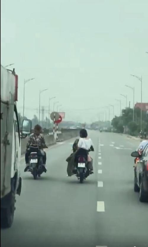 Không chỉ dàn hàng ngang trên đường, không cho phương tiện khác vượt lên, nhóm thanh niên này còn không đội mũ bảo hiểm khi điều khiển phương tiện giao thông. Ảnh cắt từ clip