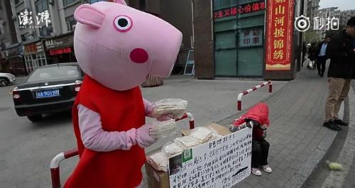Ông bố trẻ diện đồ heo Peppa bán bánh ở cổng viện với tấm biển kể lại tình cảnh bệnh tình của con gái.  Ảnh: The Paper.