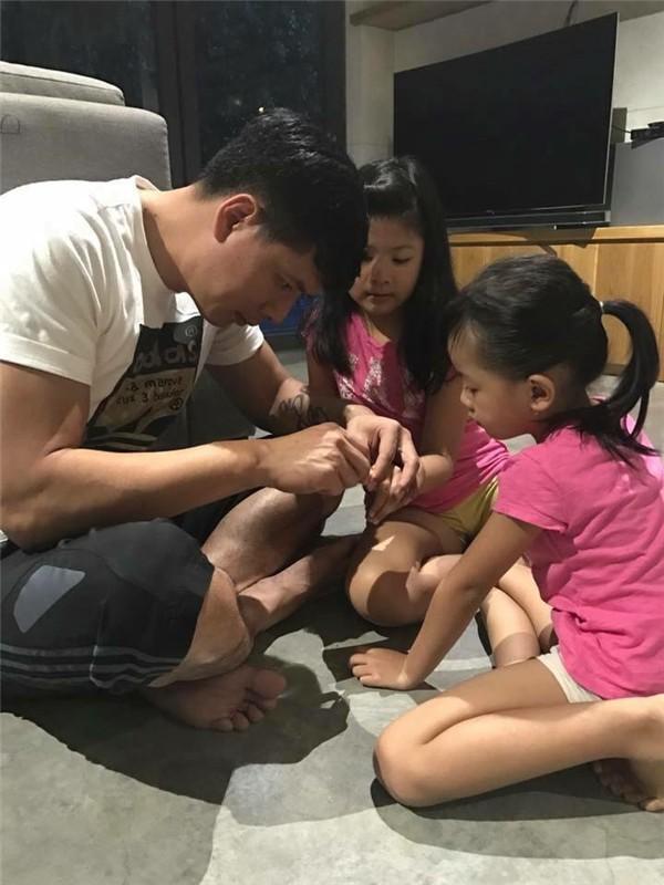 Bình Minh đang tỉ mỉ cắt móng tay cho con gái