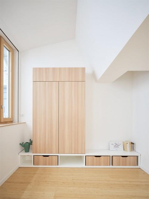 Sơn trần, tường màu trắng giúp giảm cảm giác nặng nề và vướng víu của các mảng trần lồi lõm. Hình ảnh phòng ngủ với tủ đồ bố trí gọn gàng.